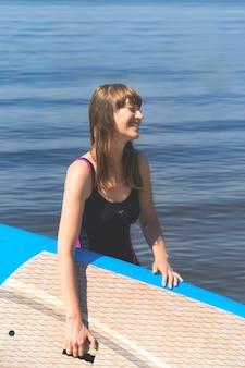 Eine schöne tausendjährige frau lächelt und hält ein bobboard in den händen, während sie am fluss steht