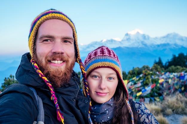 Eine schöne und aktive frau und ein bärtiger mann machen selfies beim trekking in den bergen. das konzept der aktiven erholung und des tourismus in den bergen. trekking in nepal himalaya