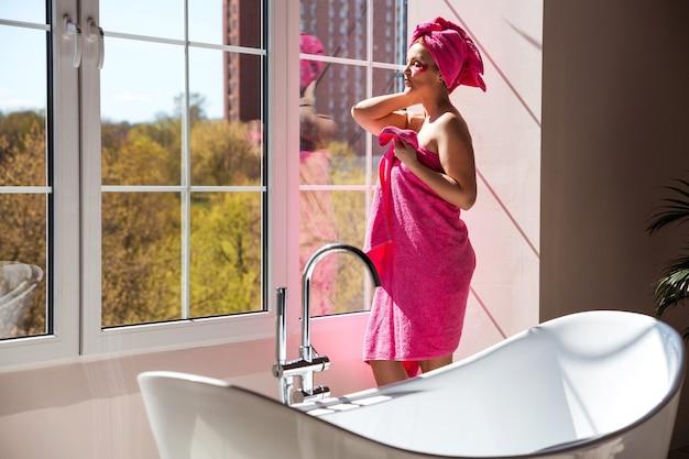 Eine schöne und glückliche frau mit einem körper und haaren, die in ein rosa handtuch gewickelt sind, posiert in einem sonnigen badezimmer. frau steht in der nähe des fensters und genießt die sonne