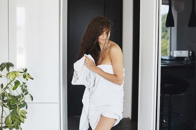 Eine schöne und schlanke junge frau, die in das duschtuch gehüllt ist, posiert zu hause im charmanten...