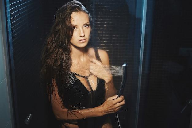 Eine schöne und schlanke junge frau duscht das charmante mädchen im bikini posiert in der duschkabine