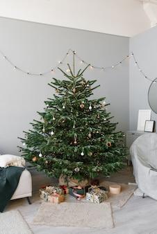 Eine schöne weihnachtsbaumtanne mit spielzeug und ein sofa mit kissen im inneren des wohnzimmers