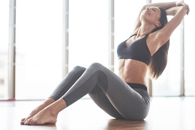 Eine schöne yoga-frau, die in einem geräumigen leichten fitnessstudio übt.