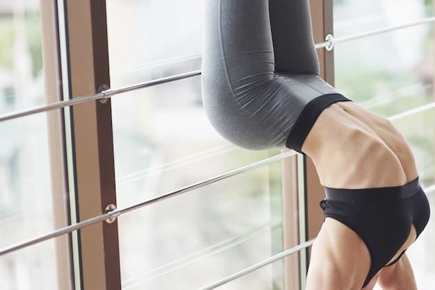 Eine schöne yoga-frau ist in der halle beschäftigt. trends auf einer sexy figur.