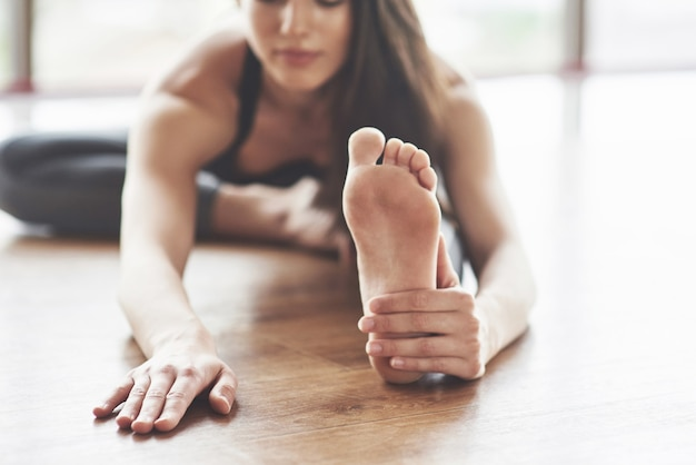 Eine schöne yoga-frau übt in einem geräumigen hellen fitnessstudio mit großen fenstern.