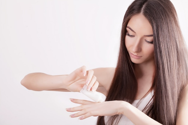Eine schönheit asien, das ein hautpflegeprodukt, eine feuchtigkeitscreme oder eine lotion und eine hautpflege verwendet, die um ihrem trockenen teint sich kümmern. feuchtigkeitscreme in weiblichen händen