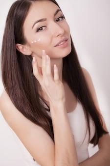 Eine schönheit asien, das ein hautpflegeprodukt, eine feuchtigkeitscreme oder eine lotion und eine hautpflege verwendet, die um ihrem trockenen teint sich kümmern.