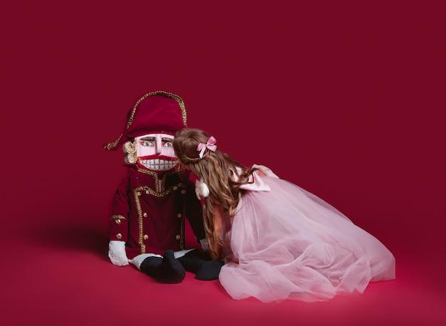 Eine schönheitsballerina, die einen nussknacker im roten studio hält