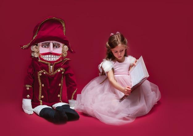 Eine schönheitsballerina, die nahe nussknacker sitzt und buch im roten studio liest