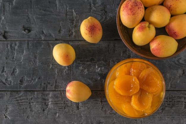 Eine schüssel aprikosen und eine schüssel marmelade auf einem holztisch.
