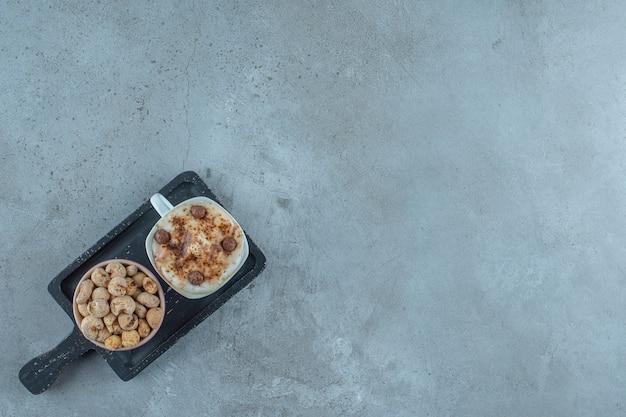 Eine schüssel cornflakes und eine tasse cappuccino auf einem brett auf blauem hintergrund.