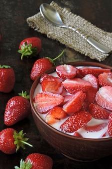 Eine schüssel erdbeeren mit sahne. bunter gesunder nachtisch. keto-diät. keto-dessert