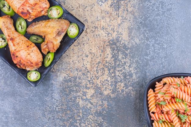 Eine schüssel fusilli-nudeln neben hühnerfleisch auf einer platte auf dem marmor.