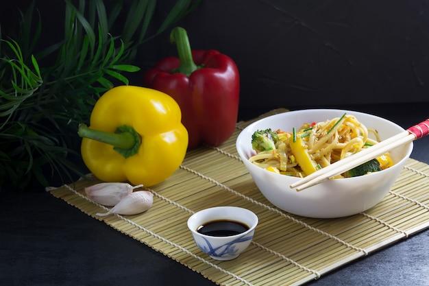Eine schüssel gebratene udon-nudeln mit gemüse und sojasauce auf einer bambusmatte