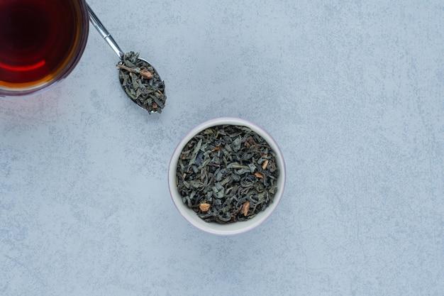 Eine schüssel getrocknete teeblätter und eine tasse tee mit einem löffel auf marmor.