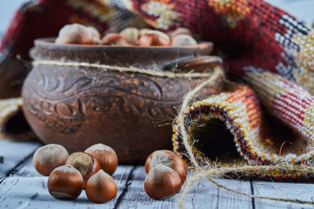 Eine schüssel haselnüsse auf blauem holztisch mit geschnitztem teppich