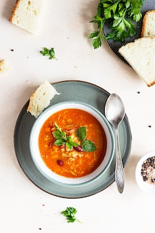 Eine schüssel hausgemachte rote bohnen-linsen-suppe, brot und petersilie. gemüsewürzige suppe.