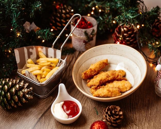 Eine schüssel hühnernuggets, serviert mit pommes frites ketchup und mayonnaise