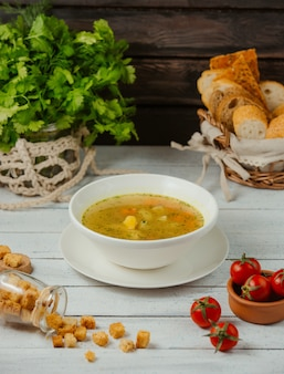 Eine schüssel hühnersuppe mit kartoffeln, karotten und dill, serviert mit brotscheiben