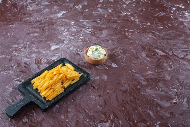 Eine schüssel joghurt und pommes frites in einem brett auf dem marmortisch.