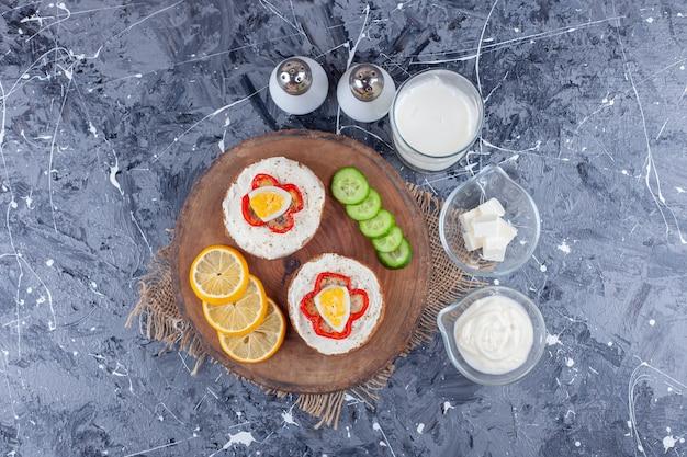Eine schüssel käse, ein glas tee neben käsebrot, zitronenscheiben und gurken auf einem brett auf dem blauen tisch.