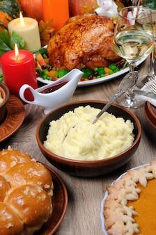 Eine schüssel kartoffelpüree auf einem tisch zwischen dem kürbiskuchen gebackener truthahn für thanksgiving