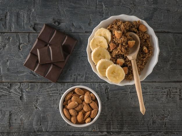 Eine schüssel mandeln, ein stück schokolade und quinoa-brei auf einem holztisch. gesunde ernährung. flach liegen.