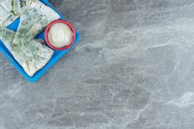 Eine schüssel mayonnaise neben gutab auf dem tablett, auf dem marmortisch.