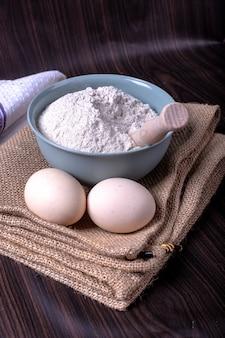 Eine schüssel mehl mit eiern auf tischdecke