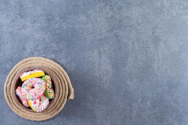 Eine schüssel mit donuts auf einem untersetzer, auf dem marmorhintergrund.