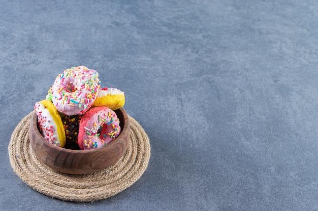 Eine schüssel mit donuts auf einem untersetzer auf der marmoroberfläche