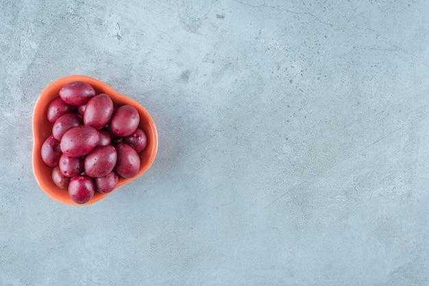 Eine schüssel mit fermentierten pflaumen, auf dem marmortisch.