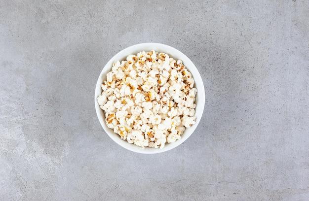 Eine schüssel mit frisch gekochtem popcorn auf marmoroberfläche