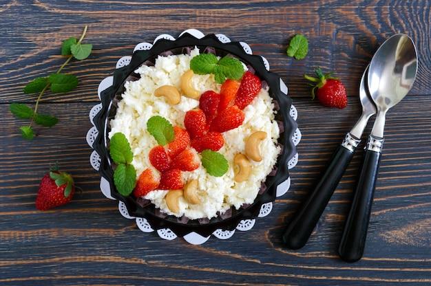 Eine schüssel mit frischem hausgemachtem hüttenkäse mit erdbeeren, minze und nüssen auf einem hölzernen hintergrund. nützliches frühstück. richtige ernährung. die draufsicht