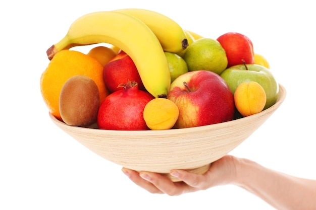 Eine schüssel mit früchten auf weißem hintergrund