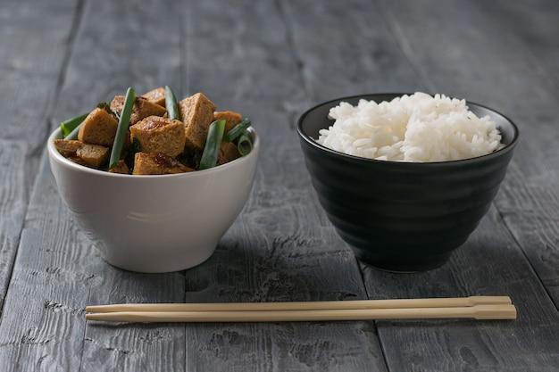 Eine schüssel mit gekochtem reis und eine schüssel mit gebratenem tofu auf einem holztisch. vegetarisches asiatisches gericht.