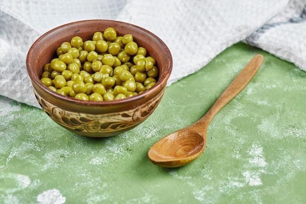 Eine schüssel mit gekochten grünen erbsen mit einem holzlöffel und einer tischdecke