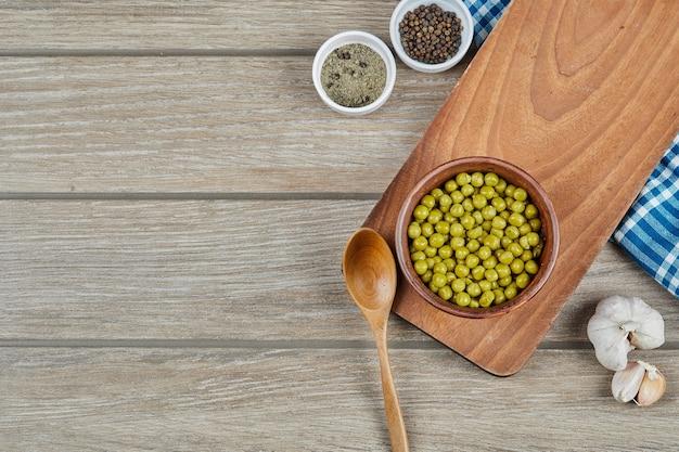 Eine schüssel mit gekochten grünen erbsen mit einem löffel, gewürzen, knoblauch und einer blauen tischdecke auf einem holztisch.