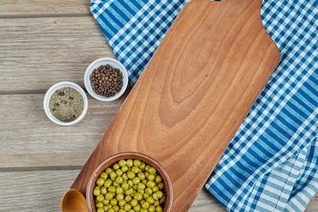 Eine schüssel mit gekochten grünen erbsen mit einem löffel, gewürzen und einer blauen tischdecke auf einem holztisch.