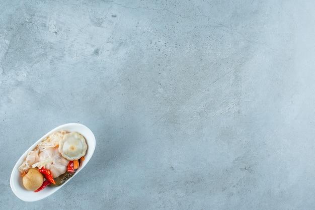 Eine schüssel mit gemischtem fermentiertem gemüse auf dem blauen tisch.