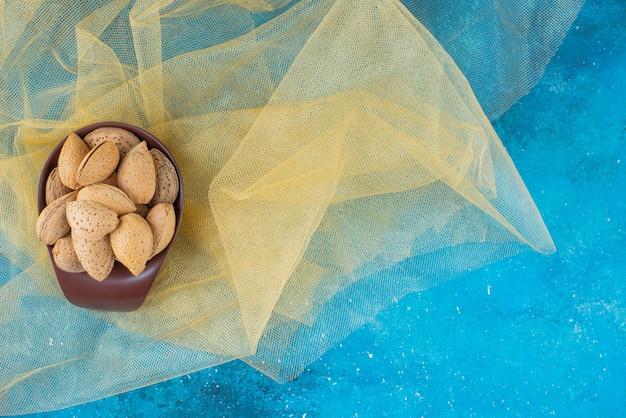 Eine schüssel mit geschälten mandeln auf tüll, auf dem blauen tisch.