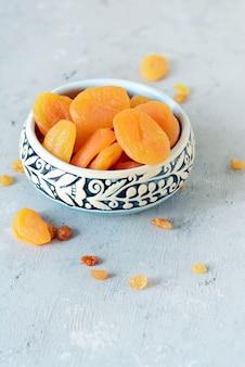 Eine schüssel mit gesunden getrockneten früchten. östliche süßigkeiten. nützliche getrocknete aprikosen für einen snack auf grauem hintergrund.