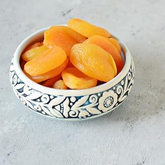 Eine schüssel mit gesunden getrockneten früchten. östliche süßigkeiten. nützliche getrocknete aprikosen für einen snack. diät, gesunde ernährung. gesundes leckeres essen, snack, arabische süßigkeiten
