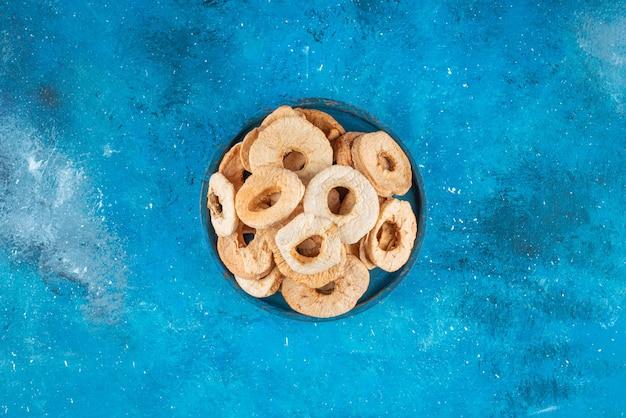 Eine schüssel mit getrockneten apfelringen auf dem blauen tisch.