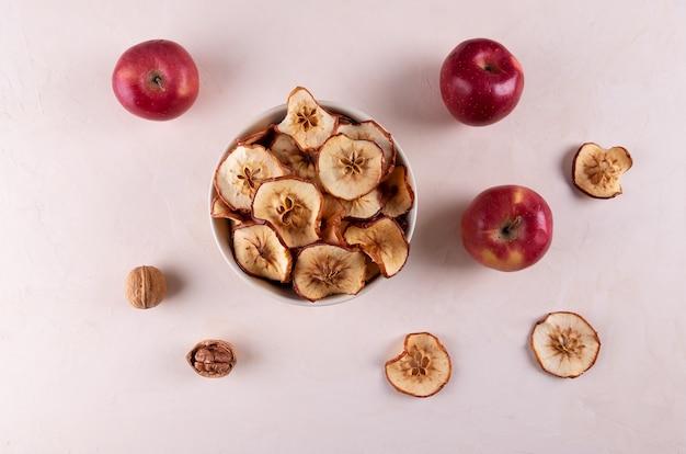 Eine schüssel mit getrockneten apfelstücken, ein paar reifen roten äpfeln und walnüssen auf einer hellen oberfläche.