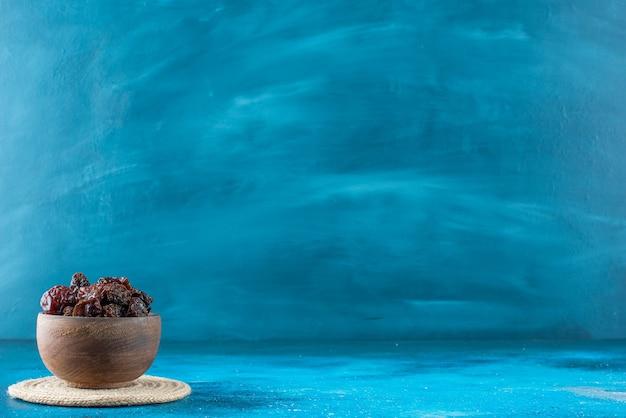 Eine schüssel mit getrockneten pflaumen auf einem untersetzer, auf dem blauen tisch.