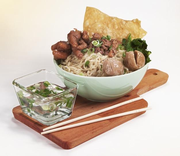 Eine schüssel mit indonesischen hühnernudeln mit hühnchen, krallen, fleischbällchen, senfgrün und frühlingszwiebeln