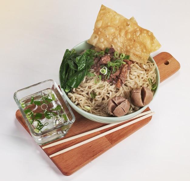 Eine schüssel mit indonesischen hühnernudeln mit hühnerstücken, fleischbällchen, senfgrün und frühlingszwiebeln