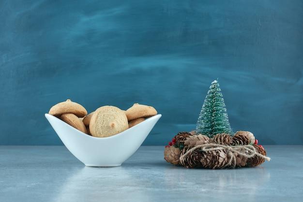 Eine schüssel mit keksen neben einer baumfigur und einem kranz auf marmoroberfläche
