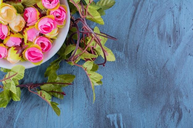 Eine schüssel mit künstlichen bunten rosen auf blau.